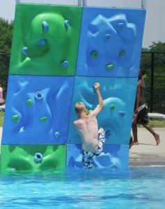 Dreng klatre på klatrevæg i svømmebassin